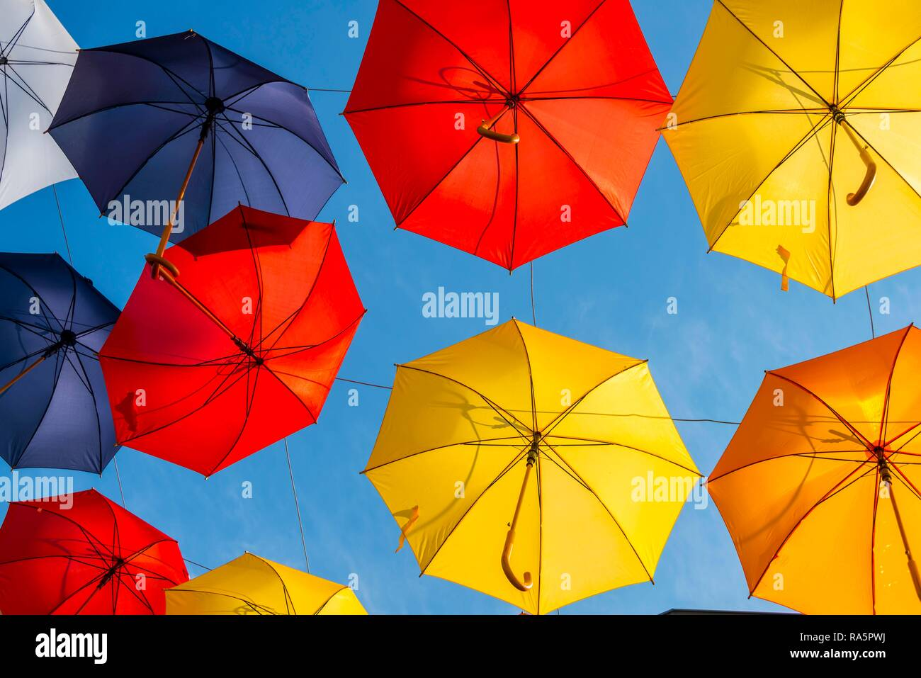 Many colorful umbrellas, parasols, hanging in the air, sunshine in front of blue sky, Imst, Tyrol, Austria - Stock Image