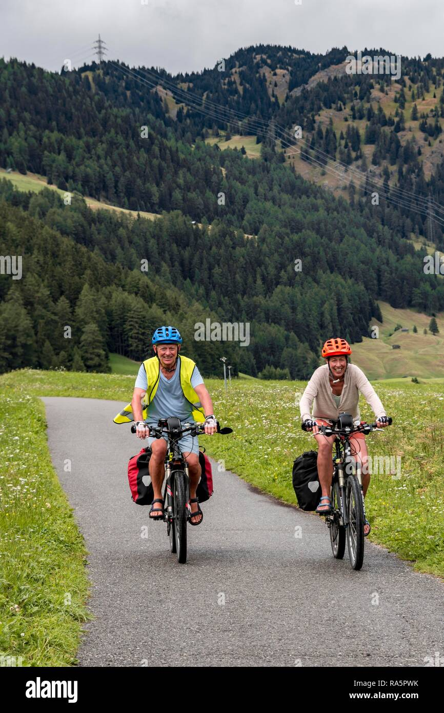 Cyclist with mountain bikes and safety vest, on the Via Claudia Augusta cycle path, crossing the Alps, Sonnenspitze at the back Stock Photo
