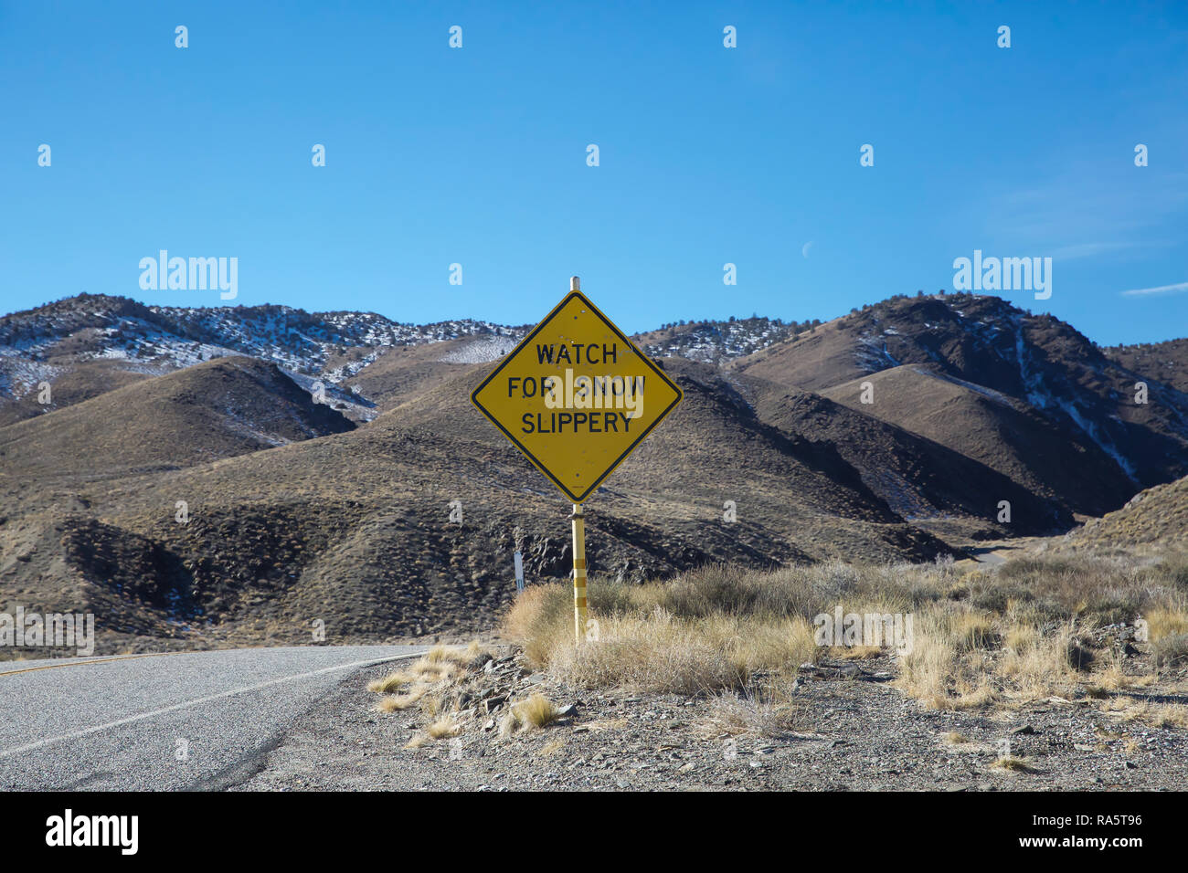 Watch for snow slippery sign on the road from Bishop in California to Las vegas Nevada,Desert, USA - Stock Image