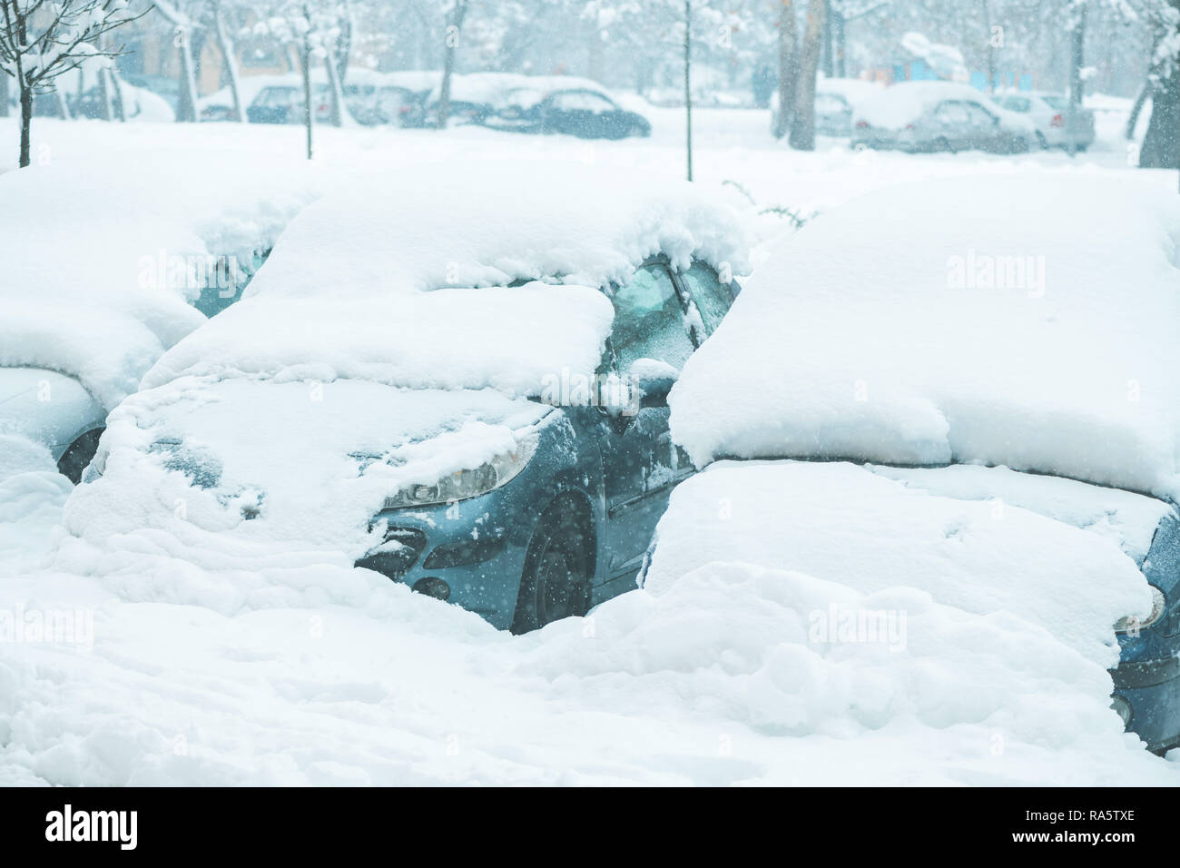 Automobile parking lot with cars covered in snow, parked vehicles in winter season with harsh traffic conditions - Stock Image