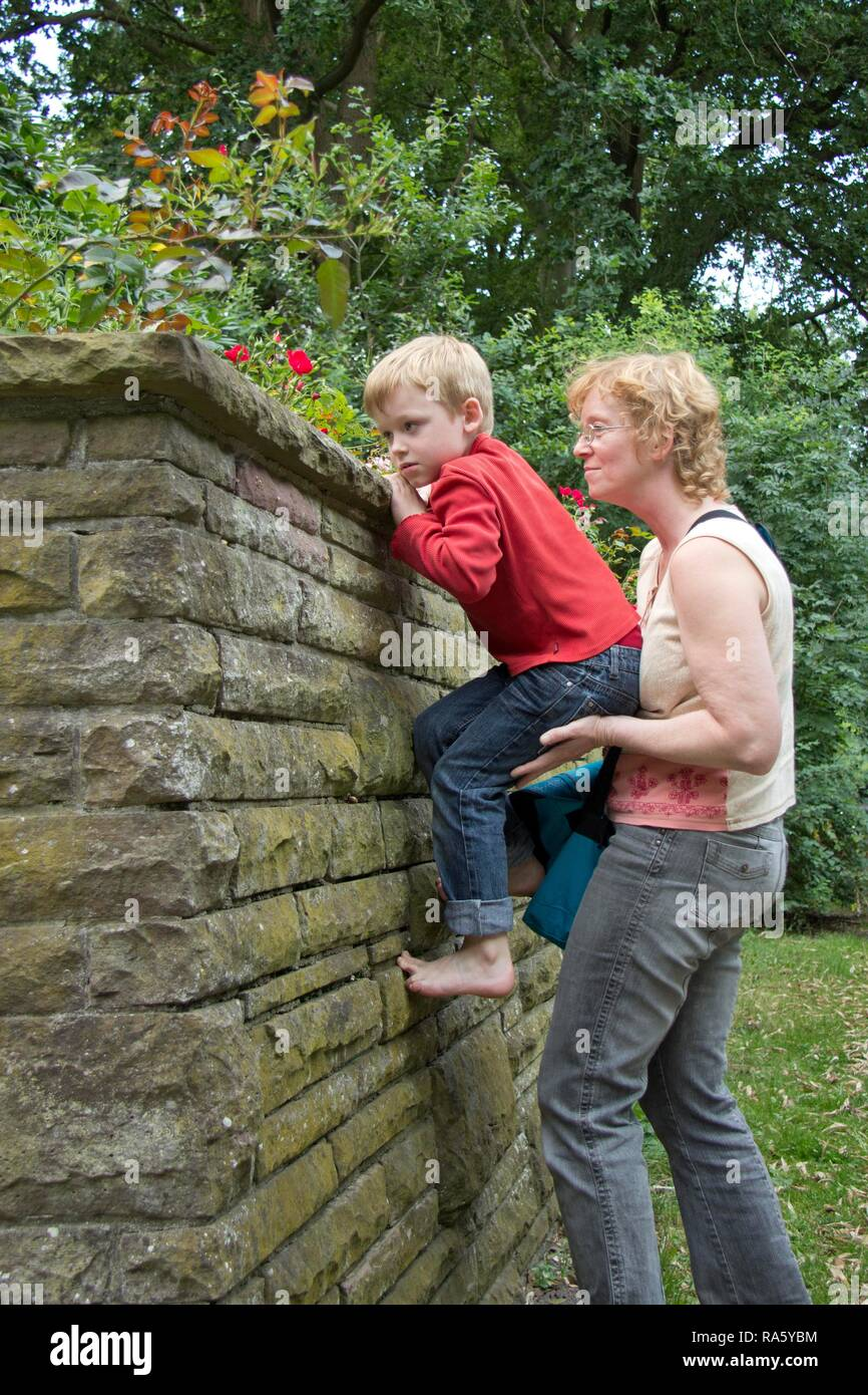 Young boy climbing a wall, supported by a woman, Seedorf, Schleswig-Holstein - Stock Image