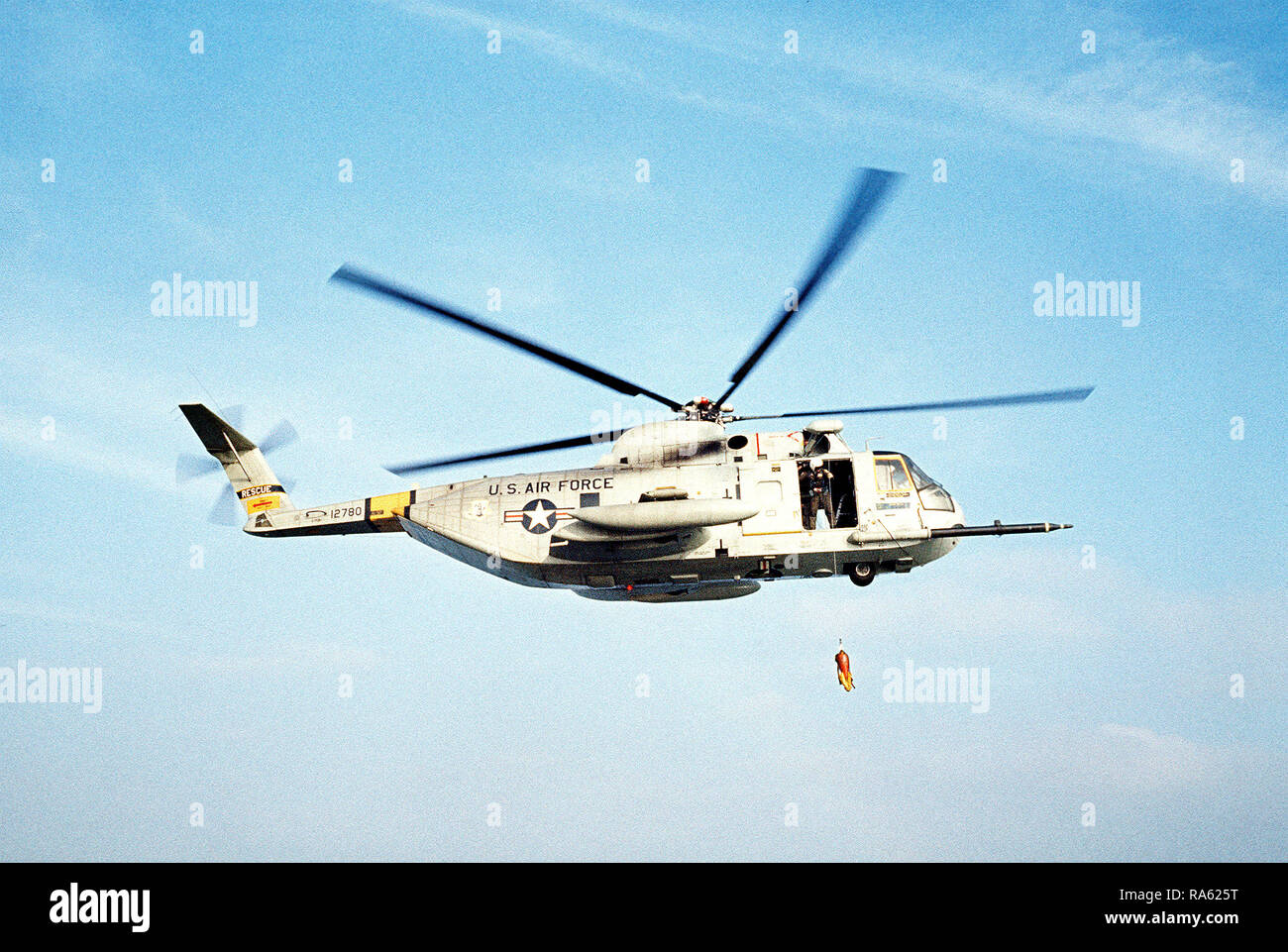 1977 - A sea-to-air right side view of an HH-3 Jolly Green Giant helicopter lowering a rescue line during a practice rescue mission off the coast of California.  The helicopter is assigned to the 129th Aerospace Rescue and Recovery Group of the Air National Guard. - Stock Image