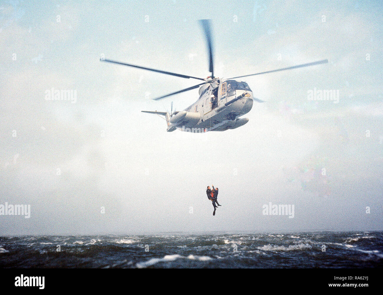 1977 - A sea-to-air view of an HH-3 Jolly Green Giant helicopter using a recovery hoist to lift two pararescuemen from the water off the coast of California.  The men, from the 129th Aerospace Rescue and Recovery Group of the Air National Guard, are participating in a practice rescue mission. - Stock Image