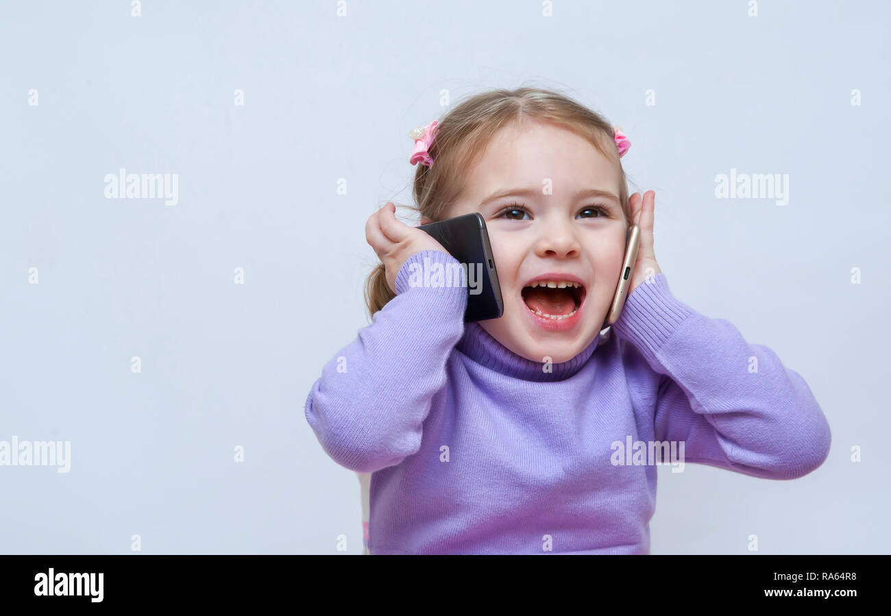 gorgeous pretty girl ispeaks on the two phones - Stock Image