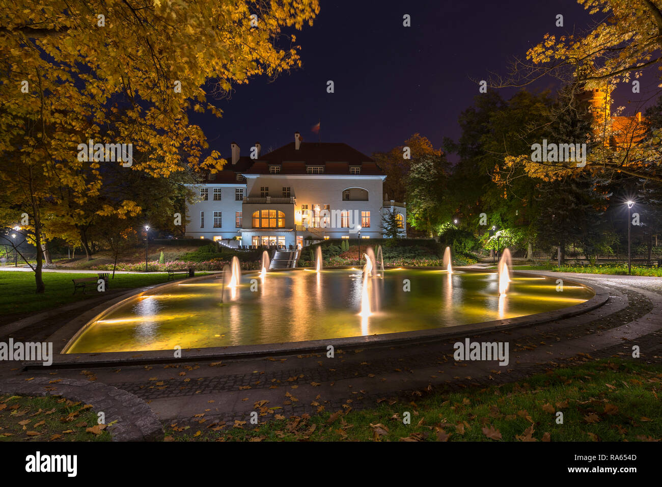 A lit fountain in a park full of autumn colors under the night sky. Poland, Olsztyn, park in the old town. - Stock Image