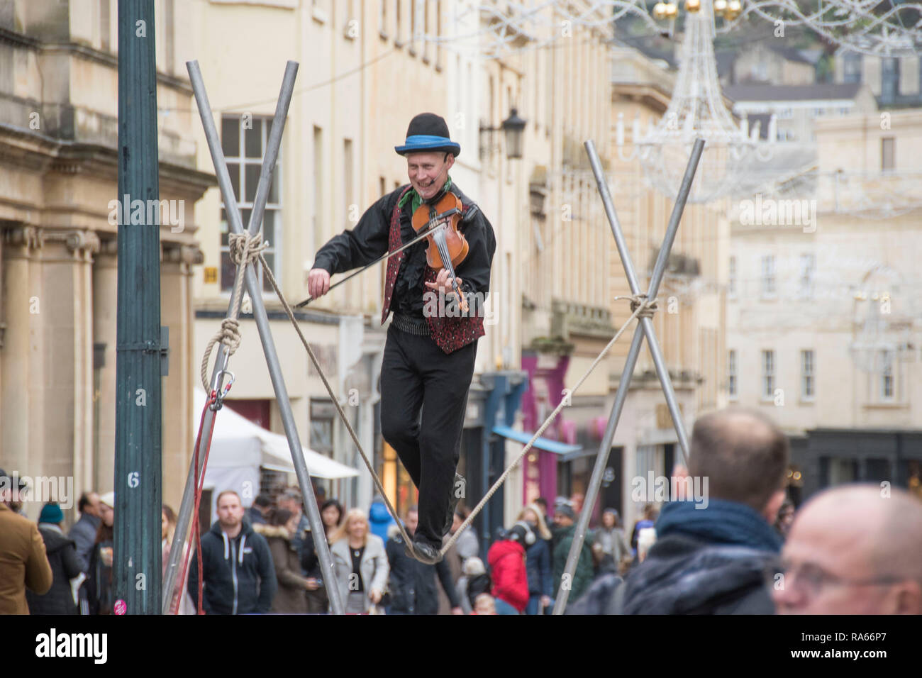 Bath, UK. 1st Jan 2019. A street entertainer plays his violin while walking on a tightrope in the centre of Bath, England on the first day of 2019 as crowds of shoppers make the most of the New Years Day sales. Credit: Phil Rees/Alamy Live News - Stock Image