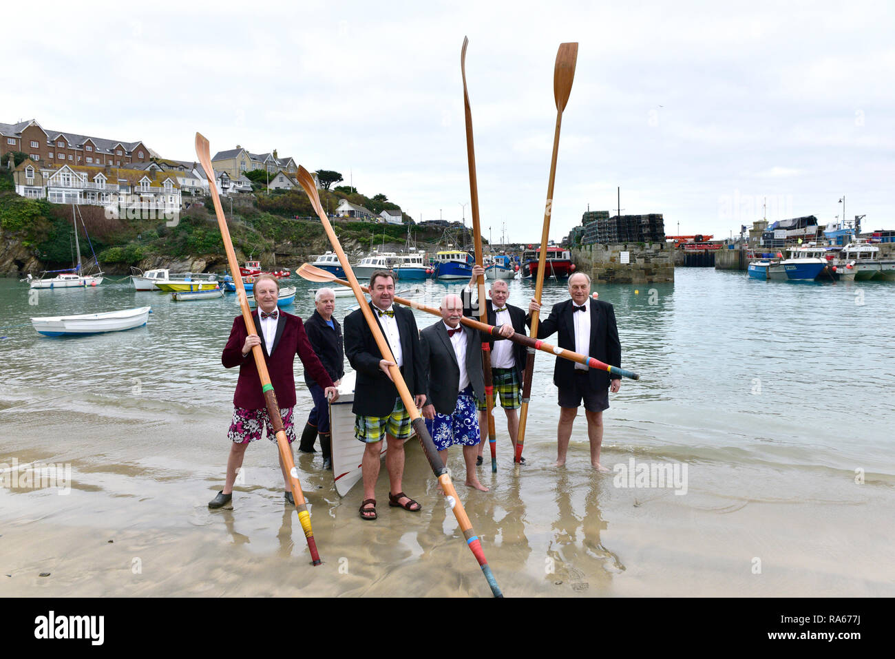 Newquay, Cornwall, UK. 21st April, 2018.  Senior members of Newquay Rowing Club wearing tuxedos prepare to set off on their annual 'Port Run'.  A bottle of port is rowed across Newquay Bay to Porth Island by these rowers in a traditional Cornish Pilot Gig.  Once they land the bottle is consumed by the rowers who then return to Newquay Harbour.   Gordon Scammell/Alamy Live News. - Stock Image