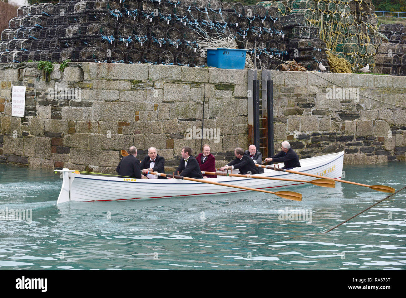Newquay, Cornwall, UK. 21st April, 2018.  Senior members of Newquay Rowing Club wearing tuxedos set off on their annual 'Port Run'.  A bottle of port is rowed across Newquay Bay to Porth Island by these rowers in a traditional Cornish Pilot Gig.  Once they land the bottle is consumed by the rowers who then return to Newquay Harbour.   Gordon Scammell/Alamy Live News. - Stock Image