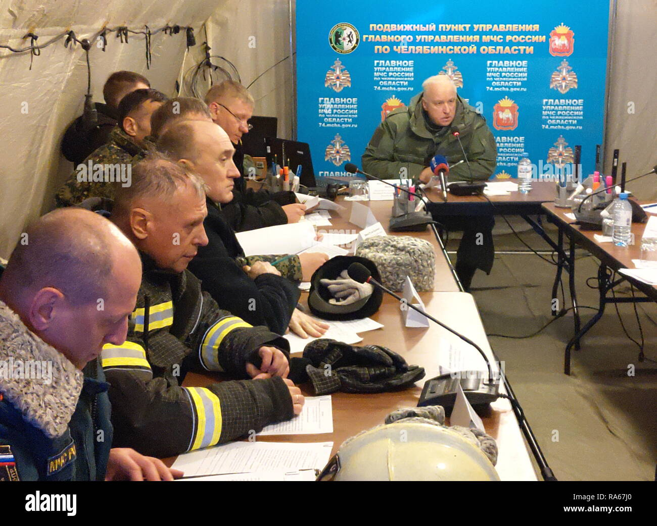 MAGNITOGORSK, RUSSIA - JANUARY 1, 2019: Russian Investigative Committee (SK) Chairman Alexander Bastrykin (R) and Chelyabinsk Region Governor Boris Dubrovsky (3rd L) at an emergency response center of the Russian Emergency Situations Ministry at the site of an apartment block collapse. On December 31, 2018, a domestic gas explosion caused a partial collapse of a residential building at 164 Prospekt Karla Marksa Street killing nine people and leaving dozens missing. Press Office of the Chelyabinsk Region Governor/TASS - Stock Image
