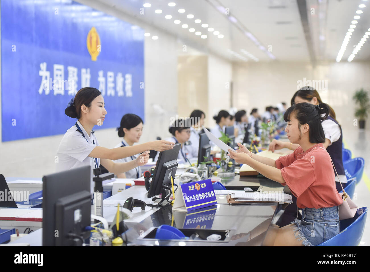 (190102) -- BEIJING, Jan. 2, 2019 (Xinhua) -- Staff members serve tax payers at the Fengze Street taxation hall of the Quanzhou tax bureau in Quanzhou City, southeast China's Fujian Province, Sept. 13, 2018. The 18th Central Committee of the Communist Party of China (CPC) held the third plenary session in November, 2013. In the five years since then, China's reform momentum had been particularly strong as the CPC decided to advance reform in all aspects during the meeting. Since the third plenary session, Chinese President Xi Jinping has presided over at least 45 high-profile meetings on advan - Stock Image