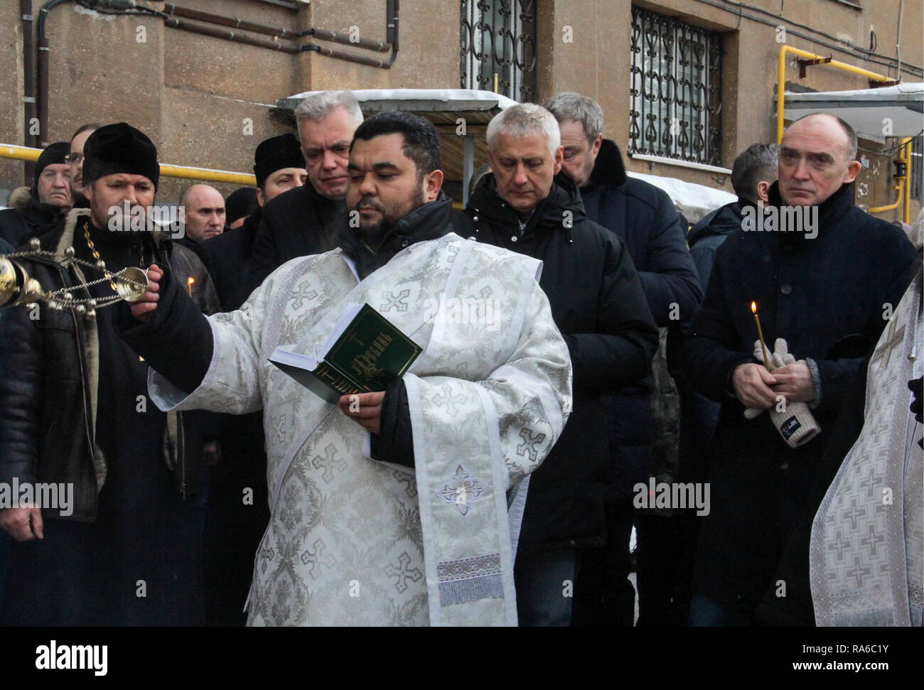 Magnitogorsk, Russia. 02nd Jan, 2019. MAGNITOGORSK, RUSSIA - JANUARY 2, 2019: Chelyabinsk Region Governor Boris Dubrovsky (R) attends an Orthodox memorial service at the site of an apartment block collapse in Magnitogorsk. On December 31, 2018, at 4:00am, a domestic gas explosion caused a partial collapse of the residential building at 164 Prospekt Karla Marksa Street killing 14 people and leaving dozens missing. Ilya Moskovets/TASS Credit: ITAR-TASS News Agency/Alamy Live News - Stock Image