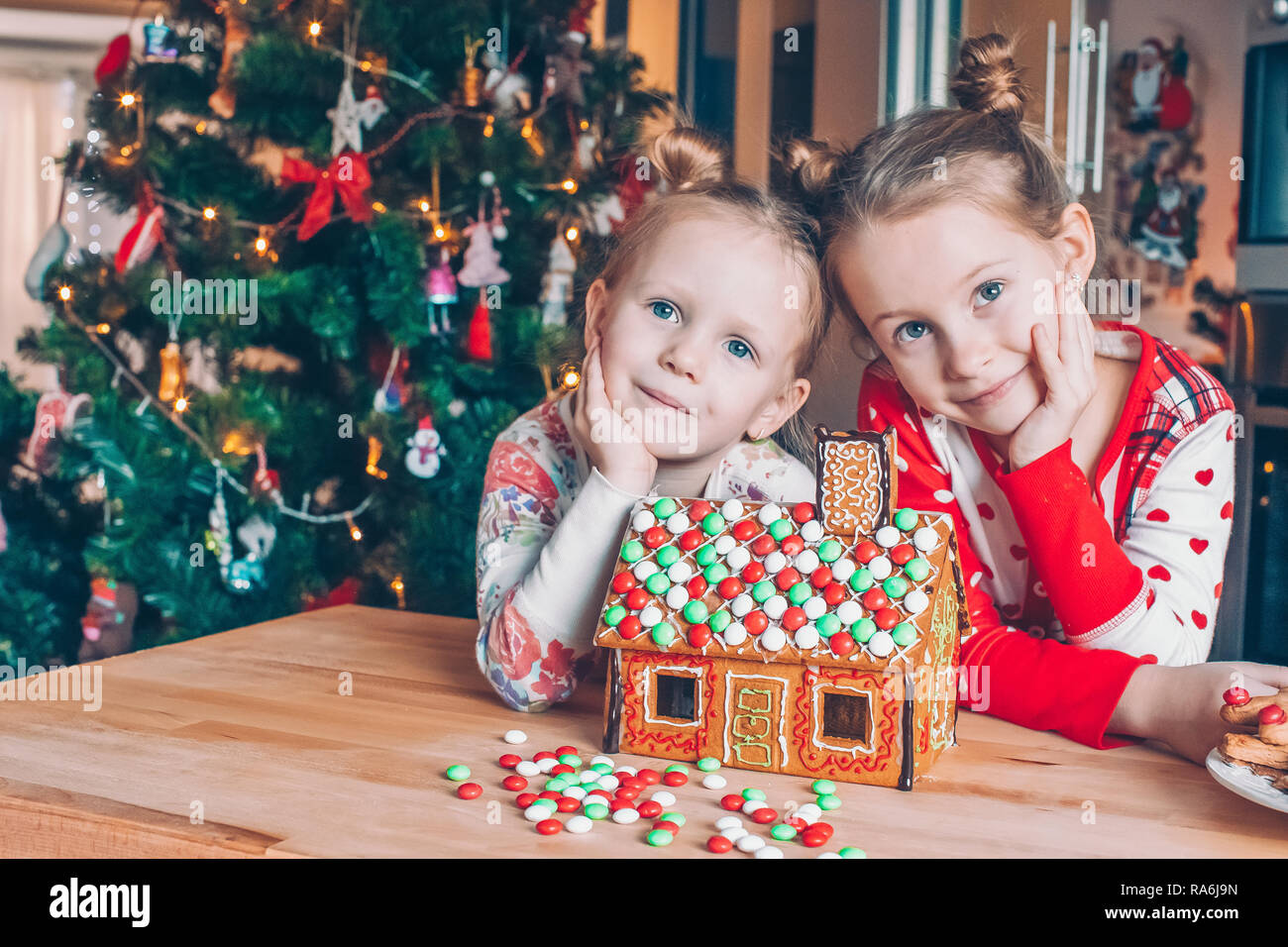 Little Girls Making Christmas Gingerbread House At Fireplace In Decorated Living Room Kids Playing With Ginger Bread Under Christmas Tree Baking And Stock Photo Alamy