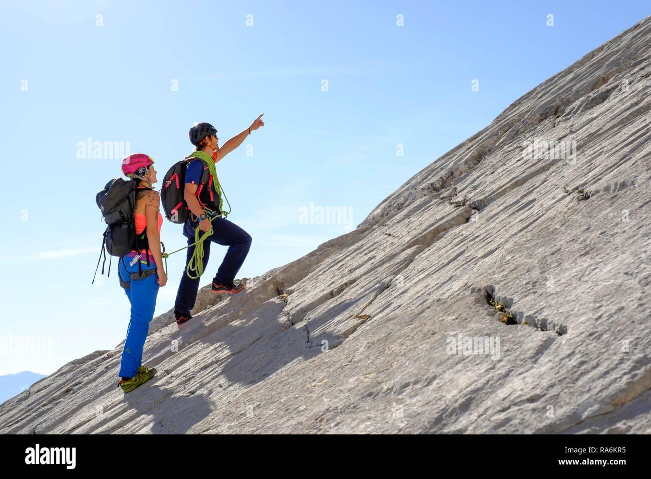 Mountain guide guiding a young woman on a short rope through a rock face, Wiederroute, Watzmann, Schönau am Königssee - Stock Image
