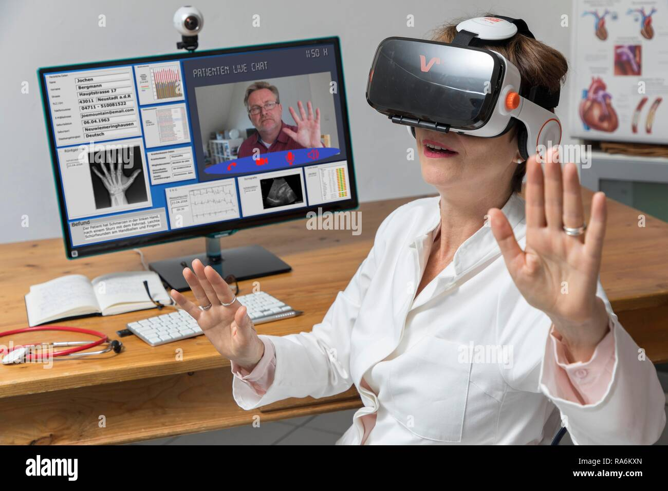 Symbol photo for telemedicine, doctor in a practice, with VR glasses, Virtual Reality, 3-D presentation of an MRT result, - Stock Image
