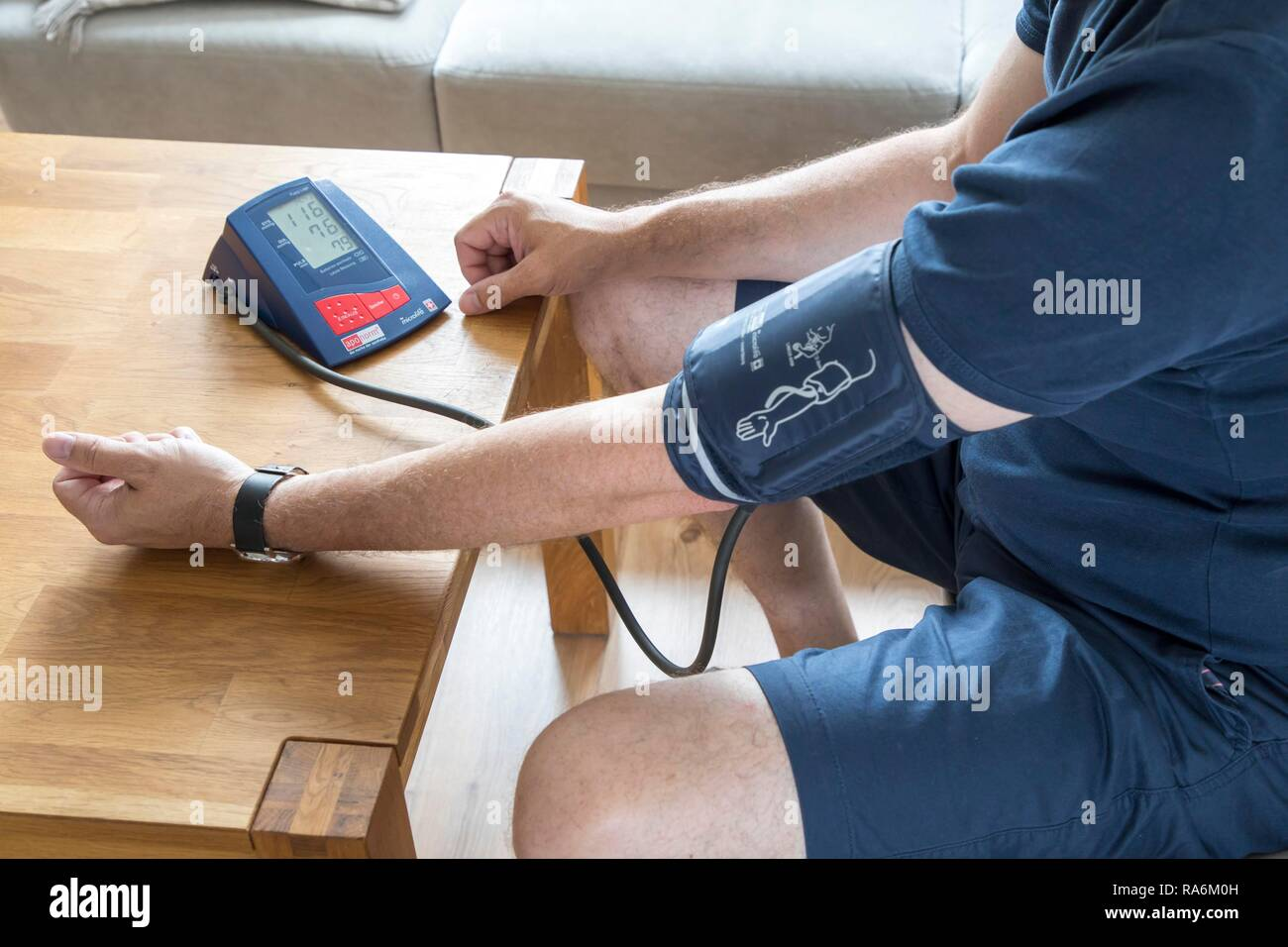 Blood pressure measurement, with an automatic upper arm blood pressure monitor, Germany - Stock Image