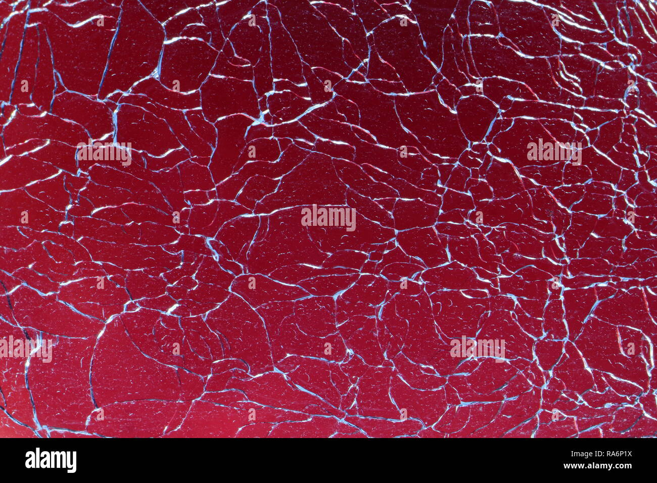 Abstract broken glass design background. Cracked, shattered glass against red background. - Stock Image