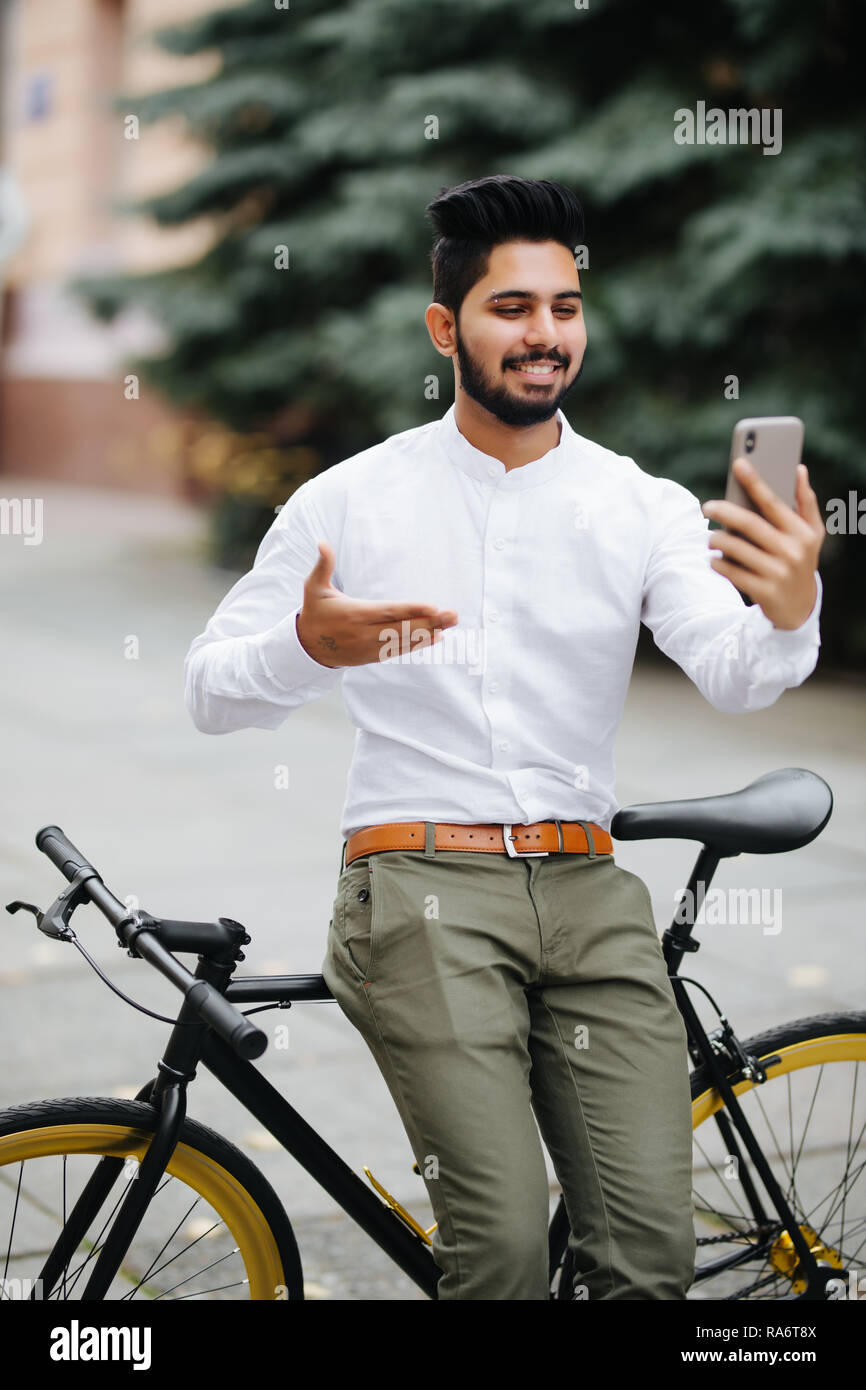 ddeab8682 Handsome indian businessman is relaxing in the city and waving to camera of  his phone having a video call while standing near his bicycle.