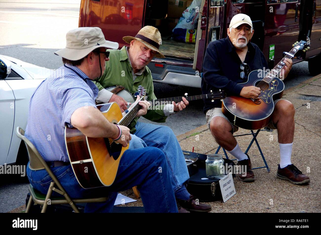 Saint Louis, MO--Sept 9, 2017; three bluegrass street musicians in hats playing guitars and a banjo outside the soulard farmers market for tips - Stock Image