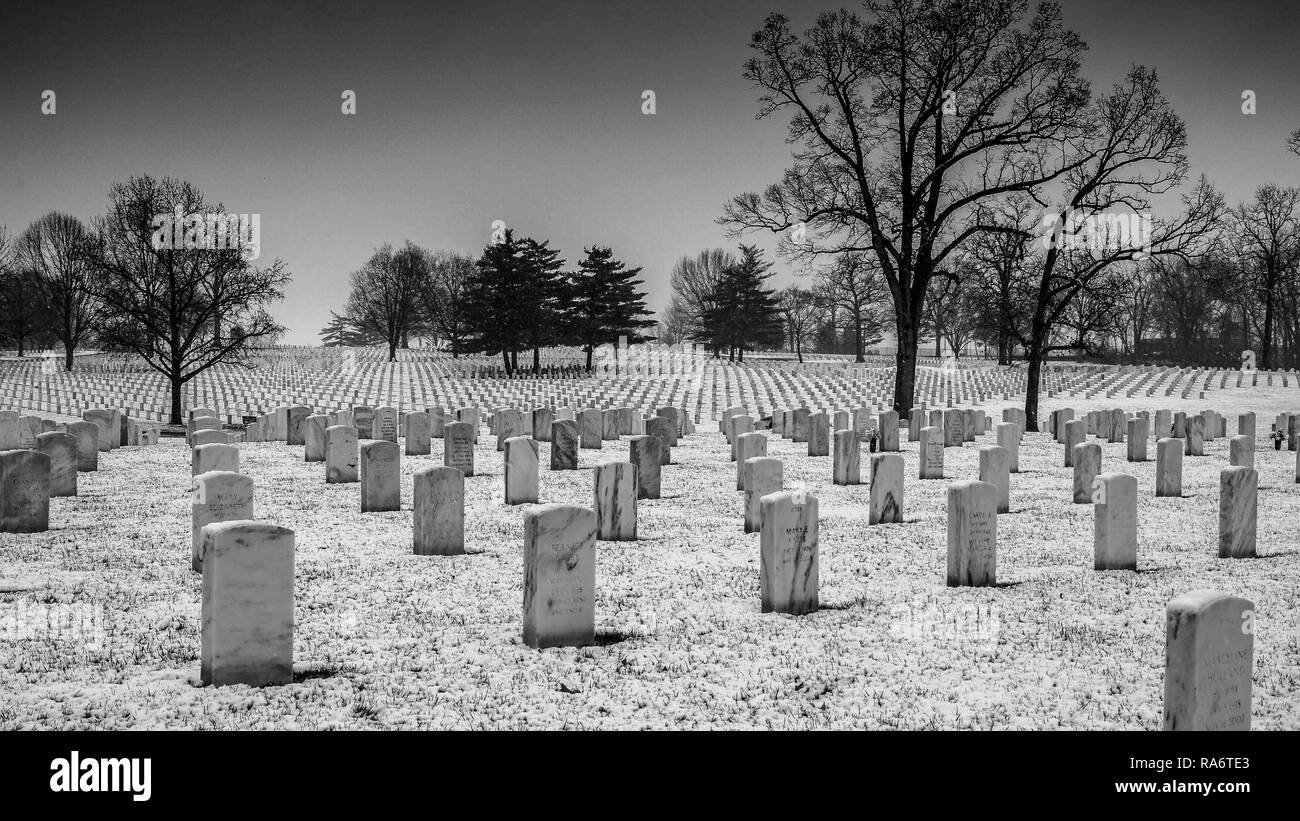 Saint Louis, MO--Mar 11, 2018; snow falling on Jefferson Barracks National Cemetery headstones, largest veterans burial gourd west of Mississippi - Stock Image