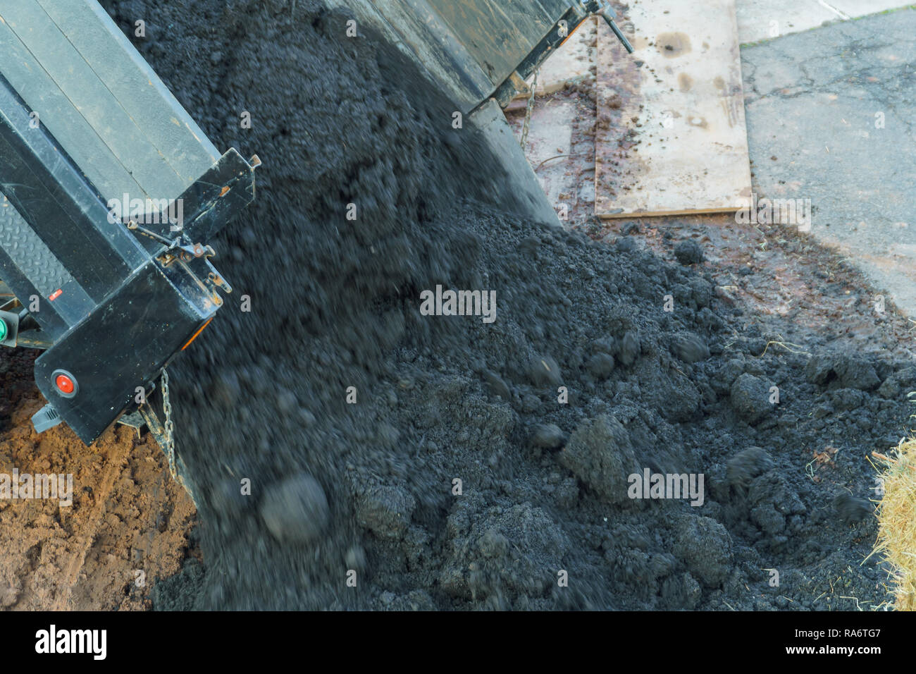 Earthworks with truck dumping and tipping raw earth soil. Tip truck preparing ground for new housing the soil and prepare for construction - Stock Image