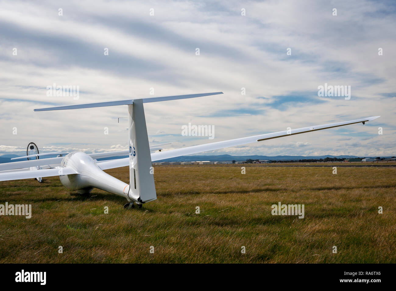 Glider on ground with a cloudy sky and hills on the horizon - Stock Image