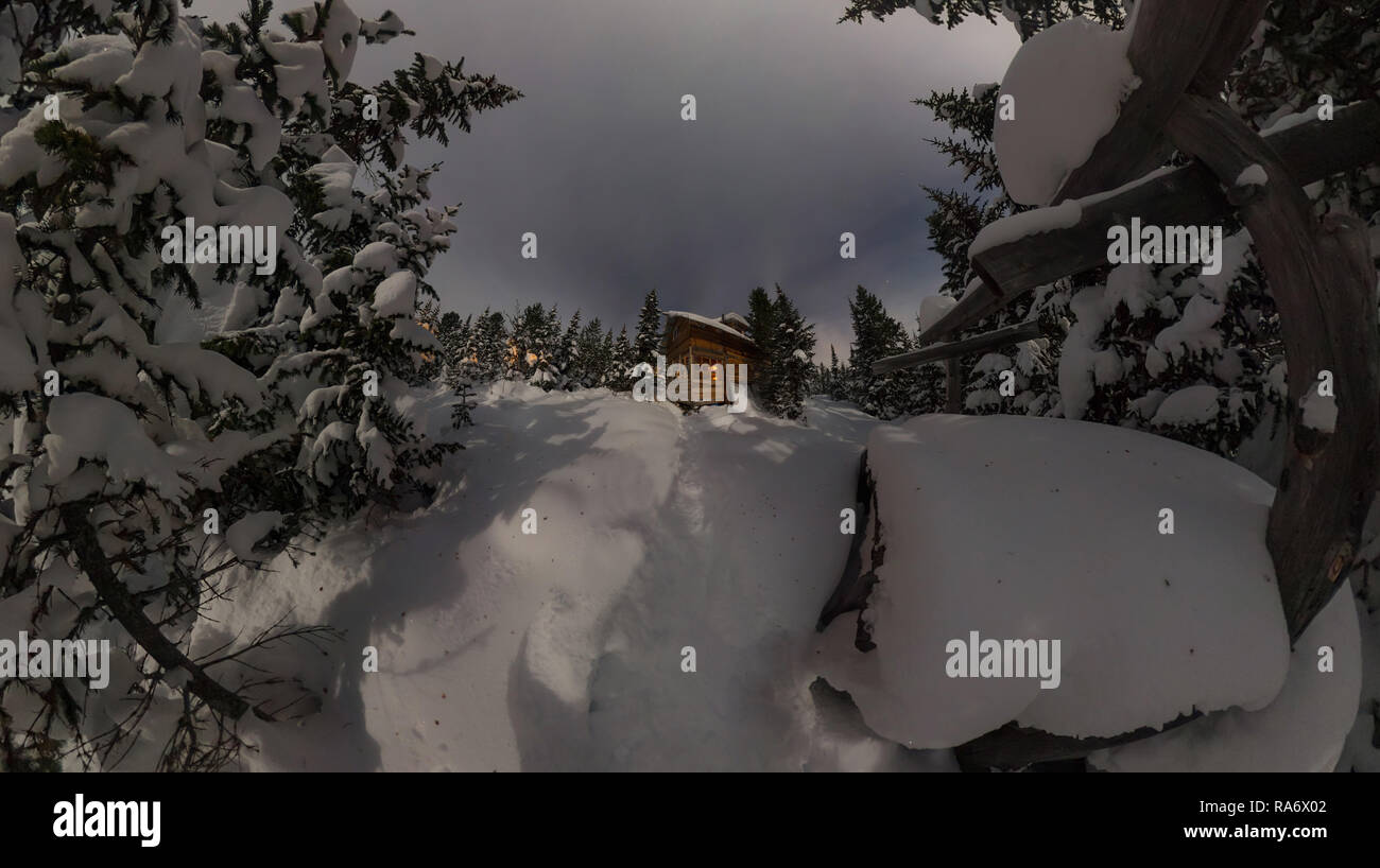Panorama house chalet during a snowfall in the trees winter forest at night in the moonlight - Stock Image
