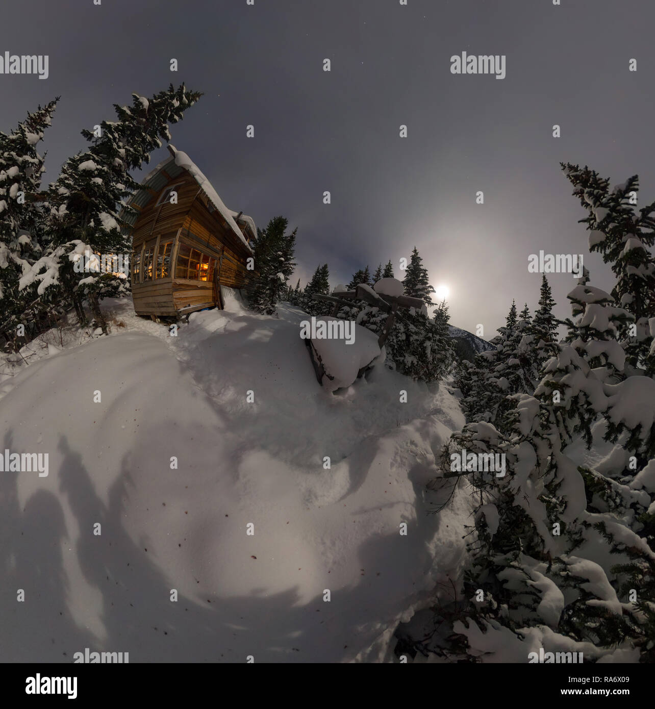 aerial view house chalet during a snowfall in the trees winter forest at night in the moonlight - Stock Image