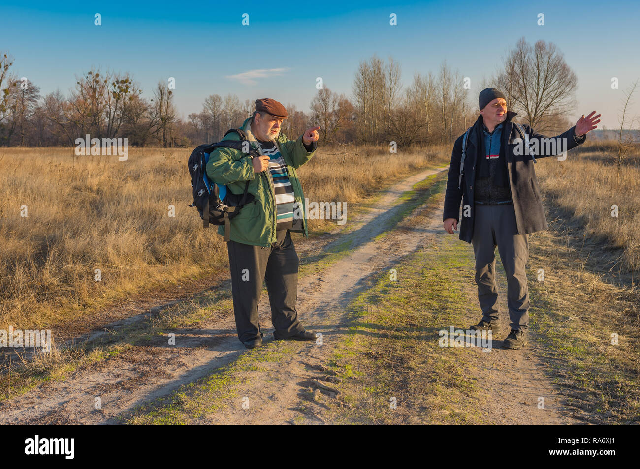 Two senior hikers with backpacks discussing correct path while walking on a country road at autumnal evening - Stock Image