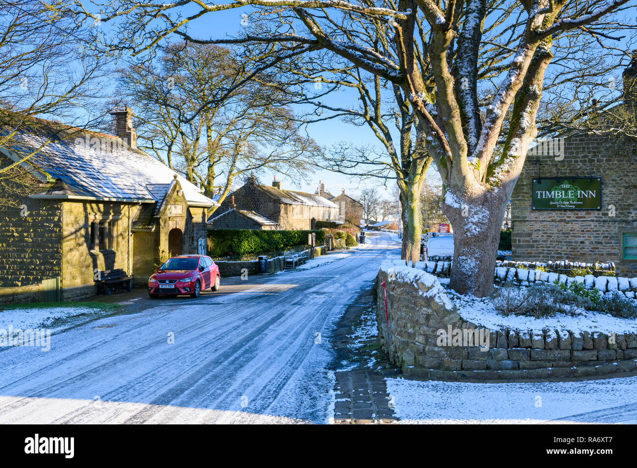 View of icy & snow covered main street (with pub & hall) in small scenic rural village on cold snowy winter day - Timble, North Yorkshire, England, UK - Stock Image