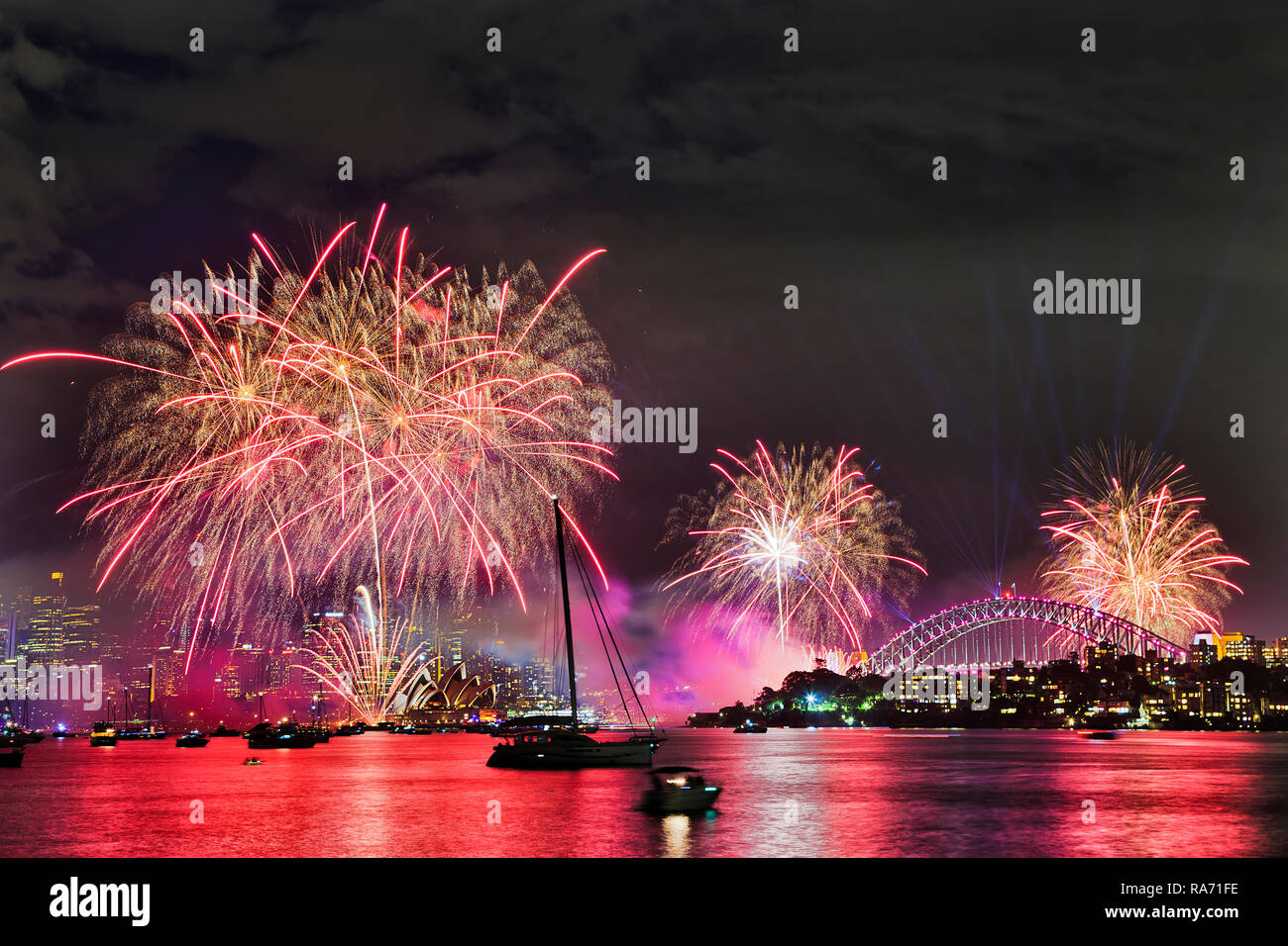 Red bright light balls of annual New Year midnight fireworks in Sydney city over waters of Sydney harbour over major city CBD landmarks. - Stock Image