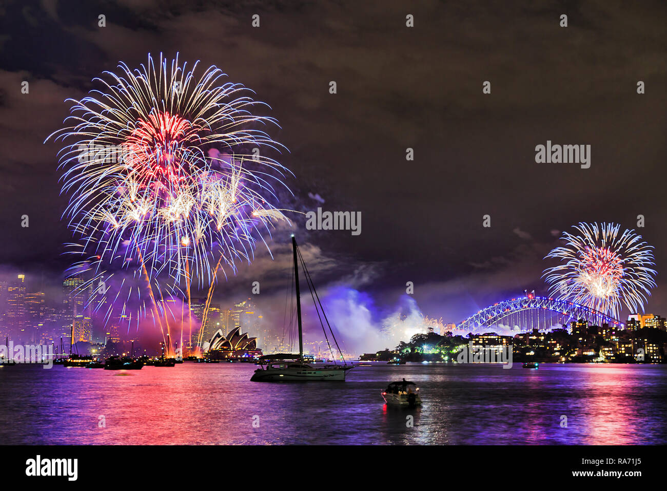 Bright light balls of annual New Year fireworks in Sydney city over CBD landmarks and reflecting in waters of Sydney Harbour. - Stock Image