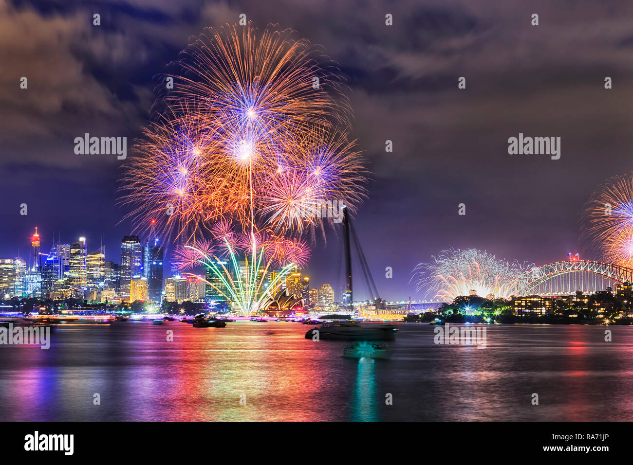 New Year eve fireworks in Sydney city over still waters of Sydney harbour reflecting bright flashing light balls. - Stock Image