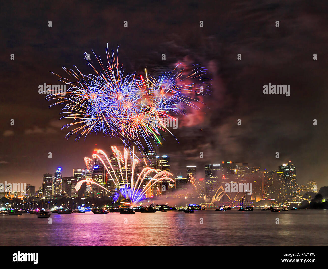 Celebration of New year with fireworks light show in Sydney city CBD with bright flashing balls over high-rise towers reflecting in still blurred wate - Stock Image