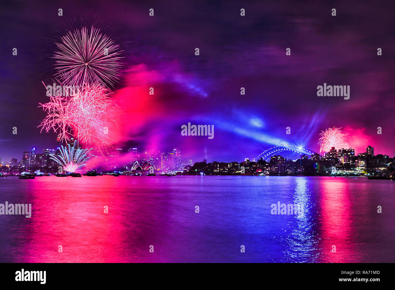 New Year Fireworks in Sydney city over CBD howers and major city landmarks when bright colour light balls reflect in still waters of Sydney Harbour. - Stock Image