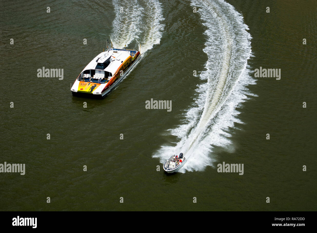 A speedboat and a CityCat ferry on the Brisbane River, Brisbane, Queensland, Australia - Stock Image