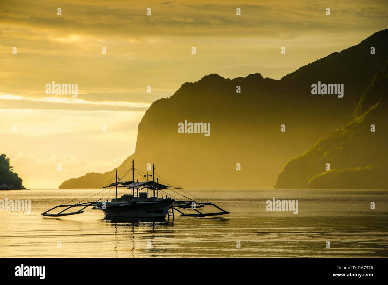 Silhouete of Outrigger at sunset in El Nido, Bacuit Archipelago, Palawan, Philippines - Stock Image