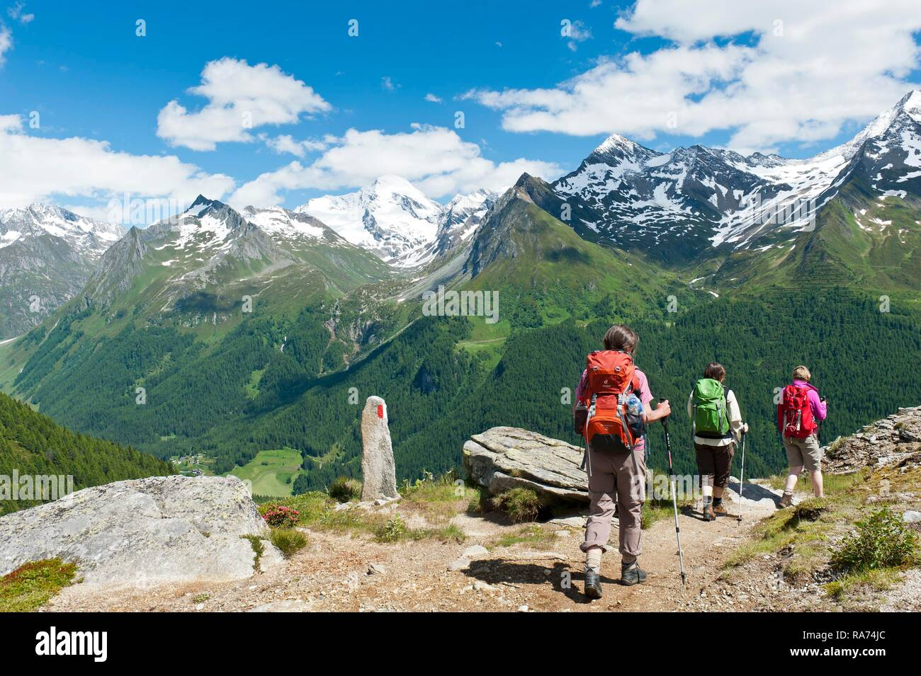Three hikers hike on a hiking trail, red and white markings on stone, snow-covered mountains, near the Waldner Alm, Kasern - Stock Image