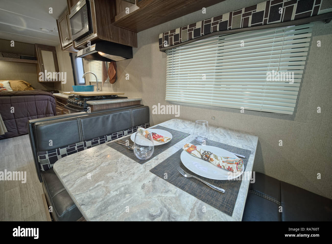 Set table inside RV travel trailer. Dining table in RV camper - Stock Image