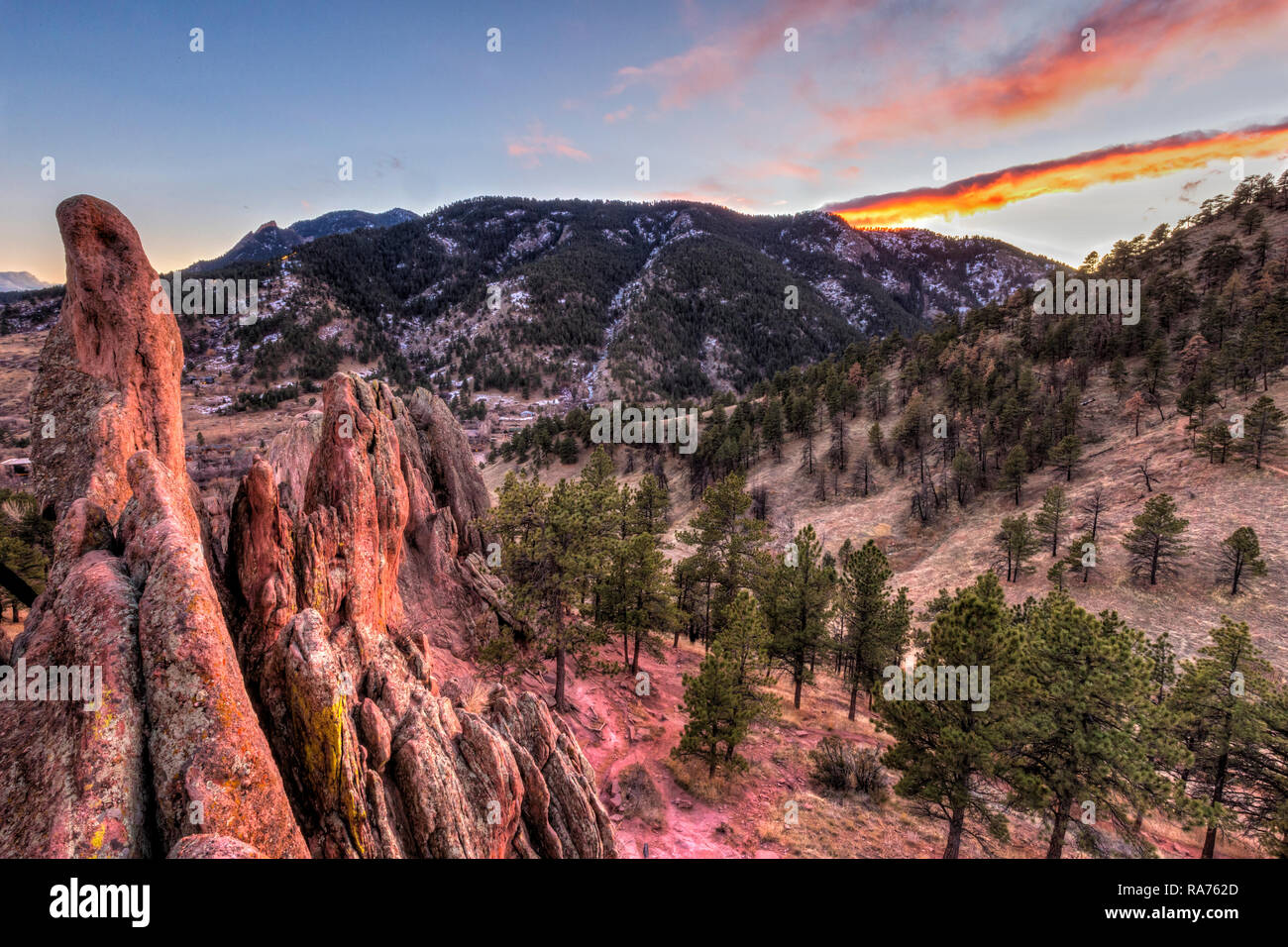 The winter sun sets behind Flagstaff Mountain, seen from the top of the Red Rock Fins in Settlers' Park in Boulder, Colorado. - Stock Image