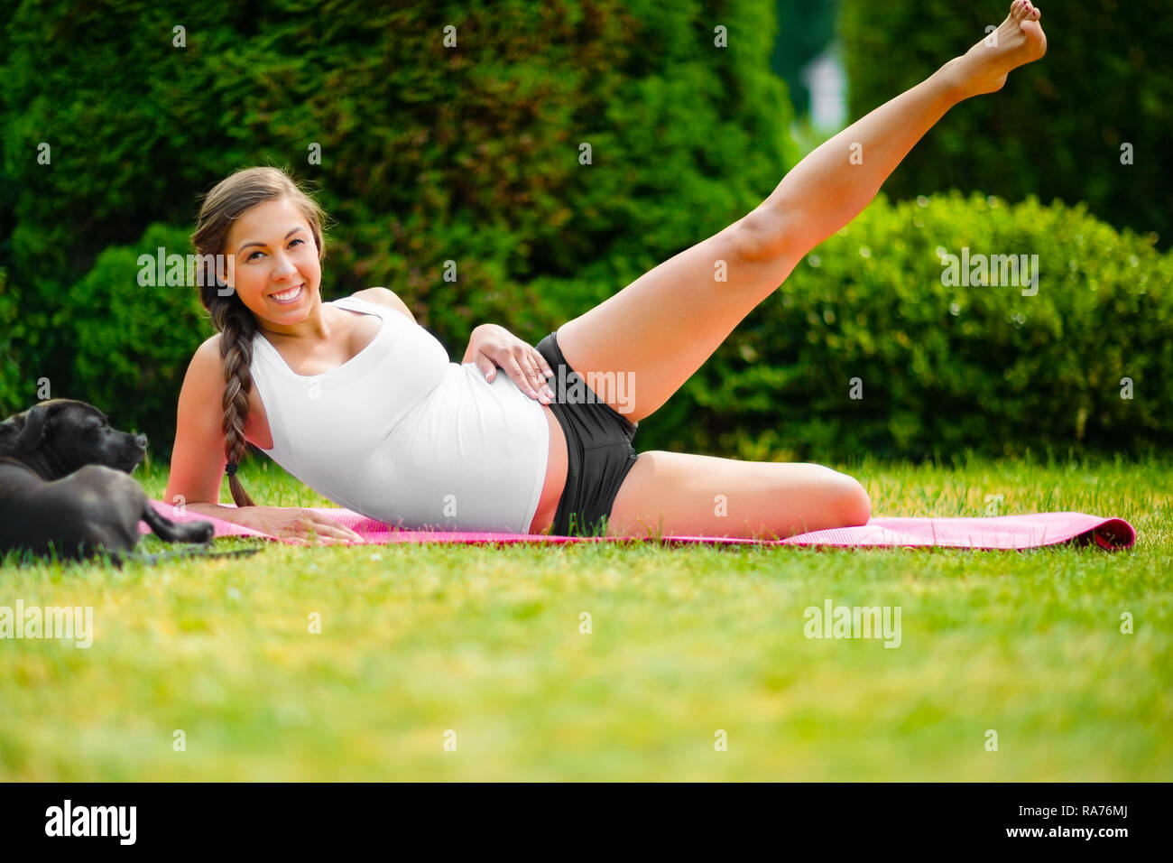 Pregnant Young Woman Performing Side Reclining Leg Lift In Park - Stock Image