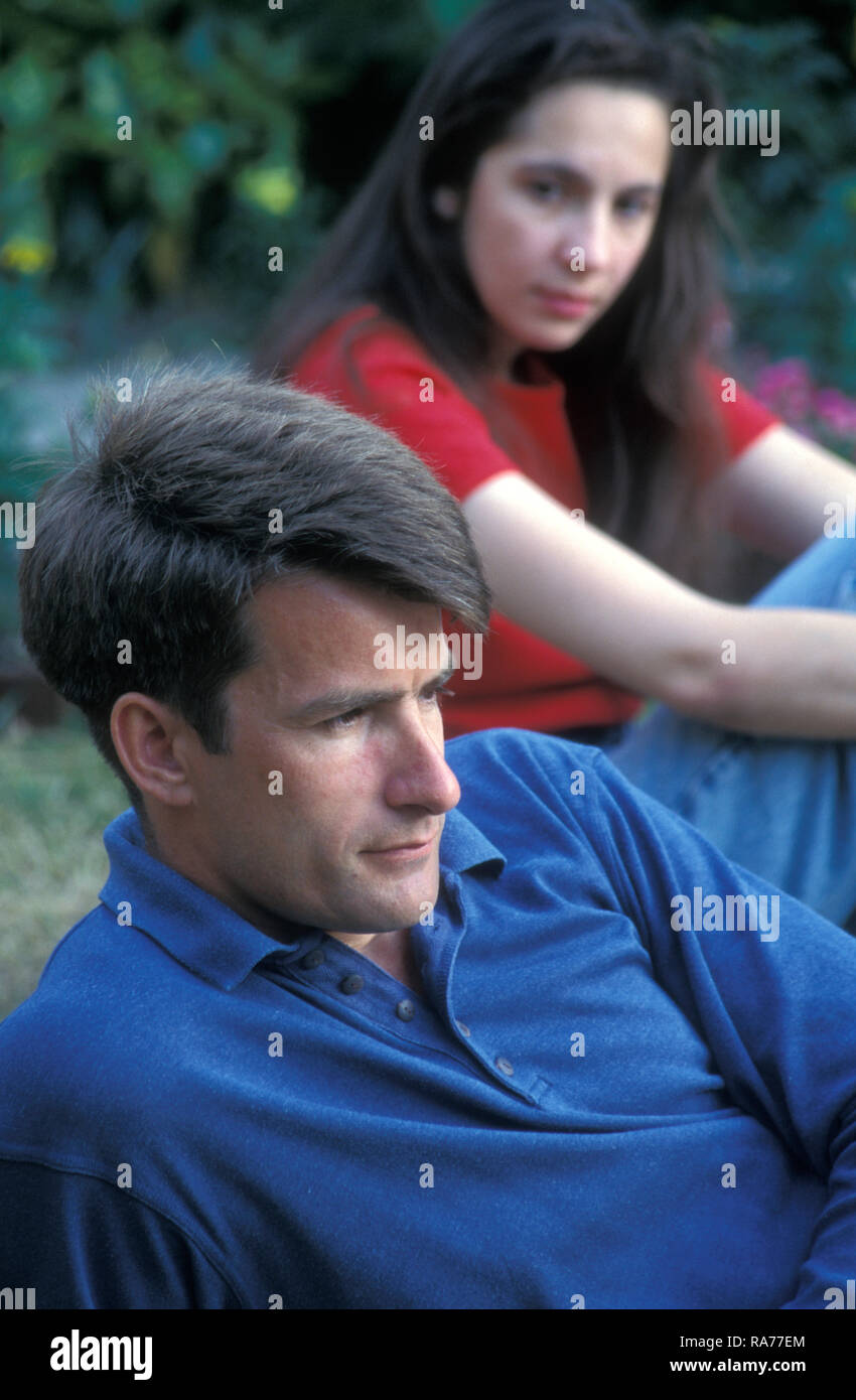 unhappy young woman glaring at her moody partner - Stock Image