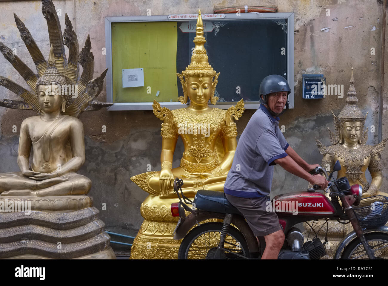 A man stops his motorbike in front of Buddha statue outside a factory for Buddha statues and religious objects, Bamrung Muang Rd., Bangkok, Thailand - Stock Image