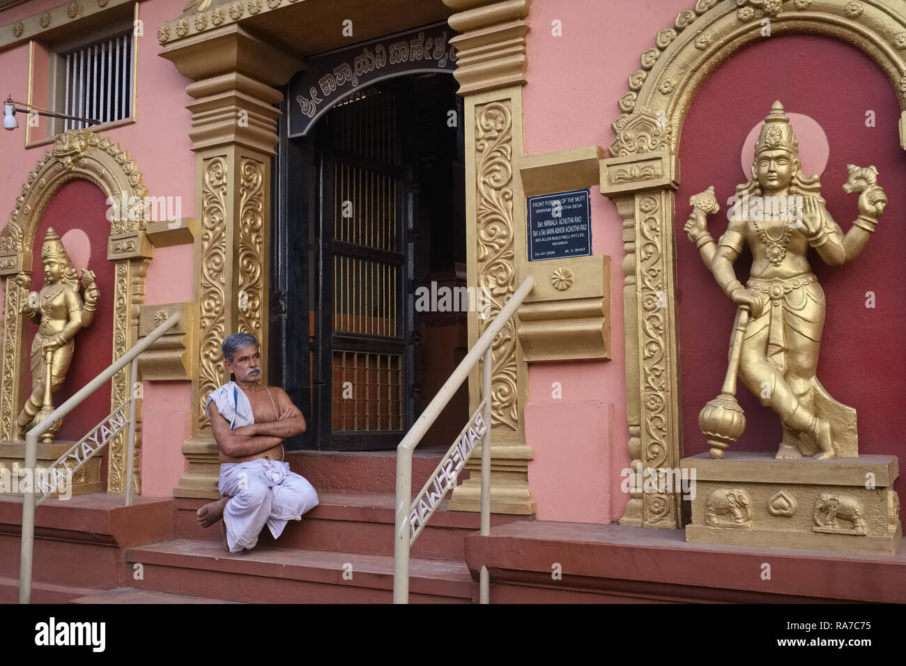 A Hindu priest relaxes outside of his temple in Mangalore, Karnataka, India, flanked by statues of Hindu deities Stock Photo