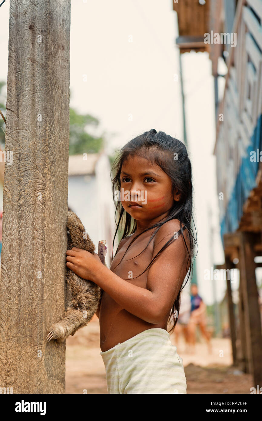 Boca de valeria, Brazil - December 03, 2015: child girl selling sloth in village. Earning money and lifestyle concept. Poverty and childhood - Stock Image