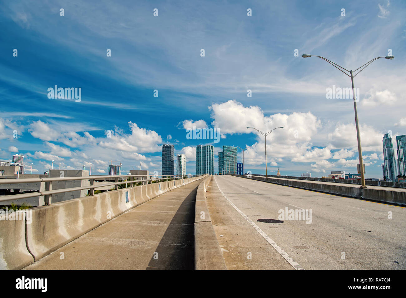 miami highway or public road roadway for transport vehicles and urban skyscrapers on cloudy blue sky background next to the port, miami dade - Stock Image