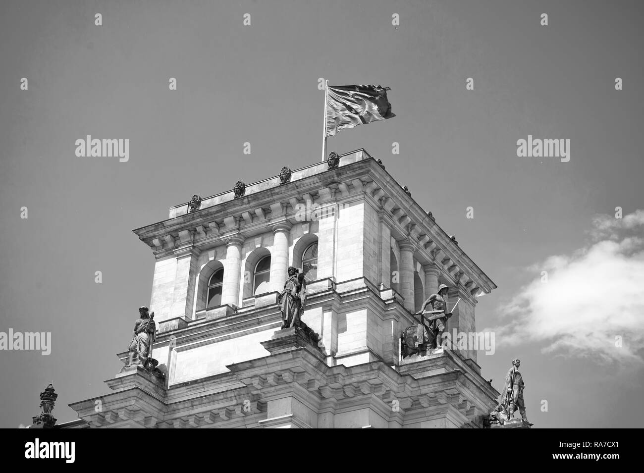 european union flag waving in the wind at famous Reichstag building berlin , seat of the German Parliament Deutscher Bundestag , on a sunny day with blue sky and clouds, central Berlin Mitte district, Germany - Stock Image
