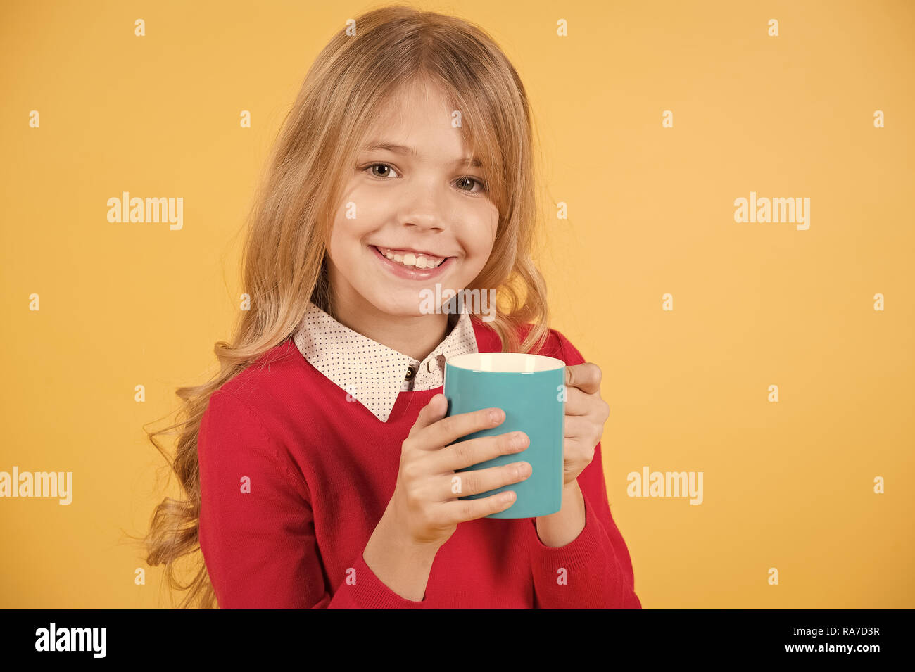 Child smile with blue cup on orange background. Girl with long blond hair in red sweater hold mug. Thirst, dehydration concept. Health and healthy drink. Tea or coffee break. - Stock Image