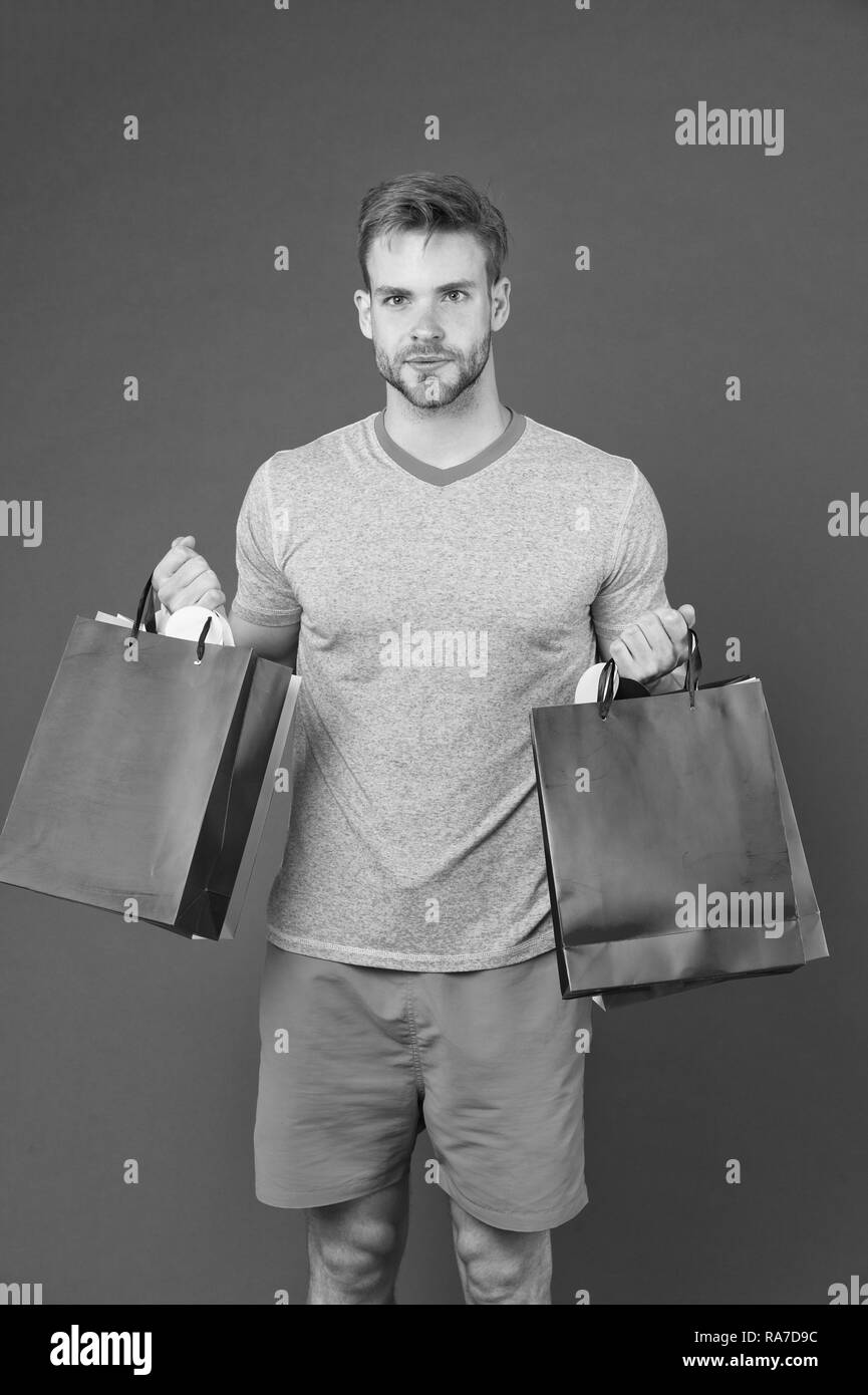 Man bearded face holds shopping bags. Guy bought lot sporty clothes and accessories. Man shopping on black friday. Guy bought lot items with discount. Seasonal sale concept. Do not miss sales. - Stock Image