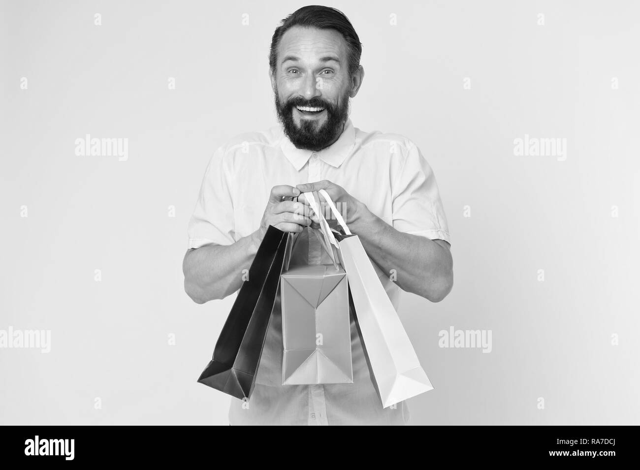 Presents make life more interesting. Man mature bearded cheerful face holds shopping bags. Man got unexpectable gifts. Guy touched by attention and gifts for him yellow background. Sincere emotions. - Stock Image