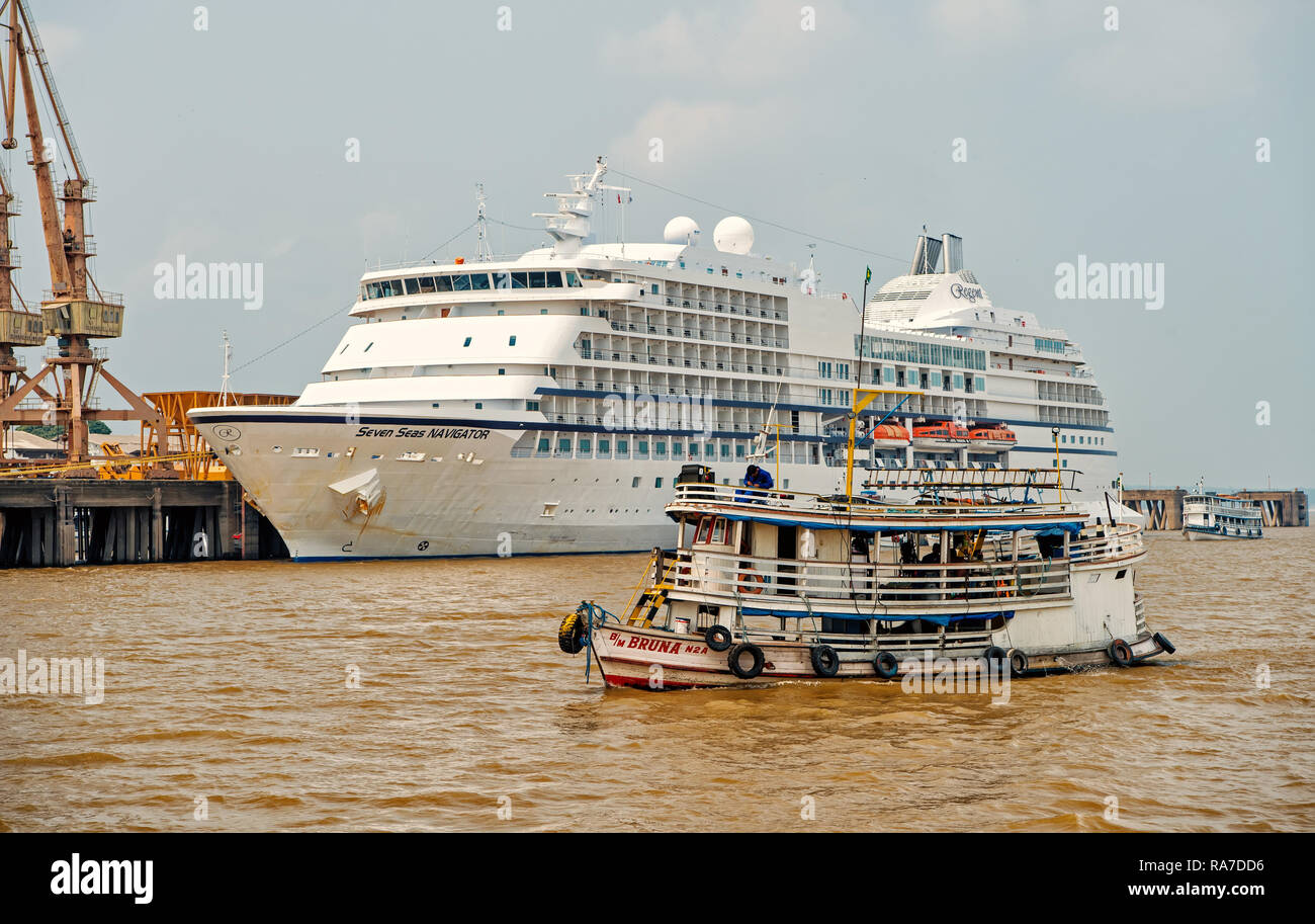 Santarem, Brazil - December 02, 2015: ship floating on sea and Seven Seas Navigator cruise liner in dock on grey sky background. Luxury lifestyle concept. Tourist destination and travelling - Stock Image